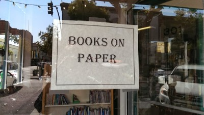 Sign in used bookstore window.